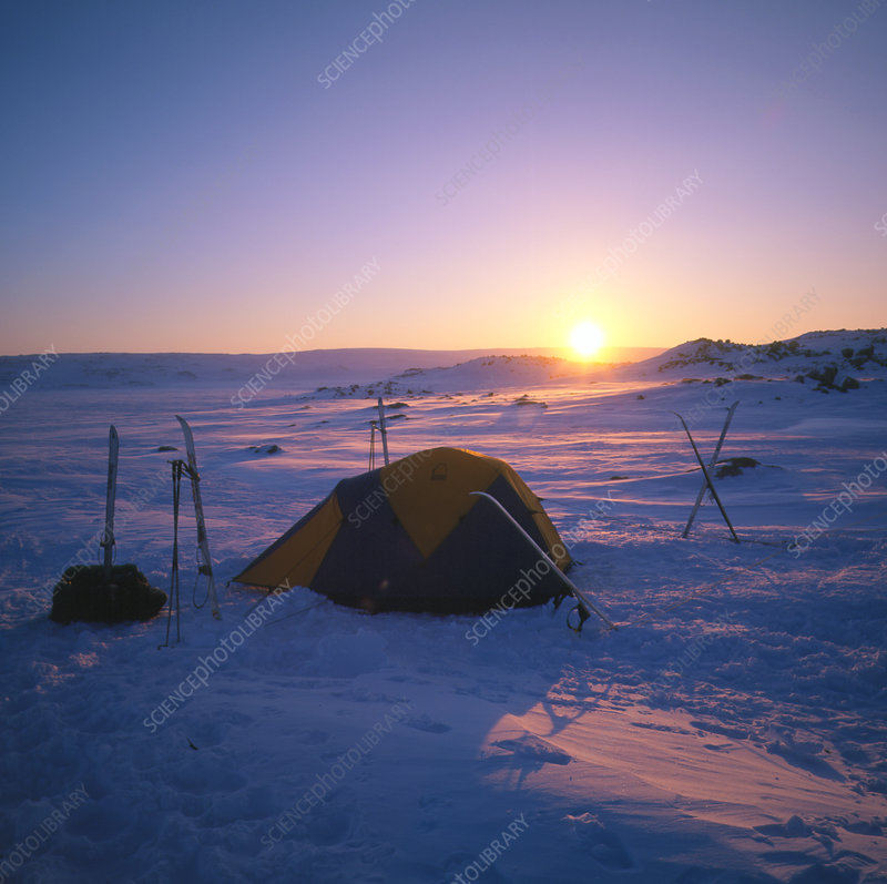 Twilight view of a campsite on snow-covered ground
