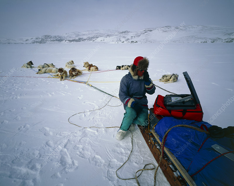 Dog sled driver resting on his sledge