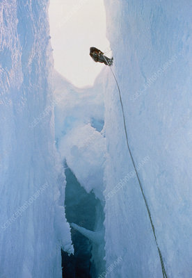 Scientist climbing down into chasm, Antarctica
