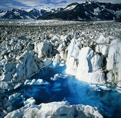 View of meltwater filling crevasses in a glacier