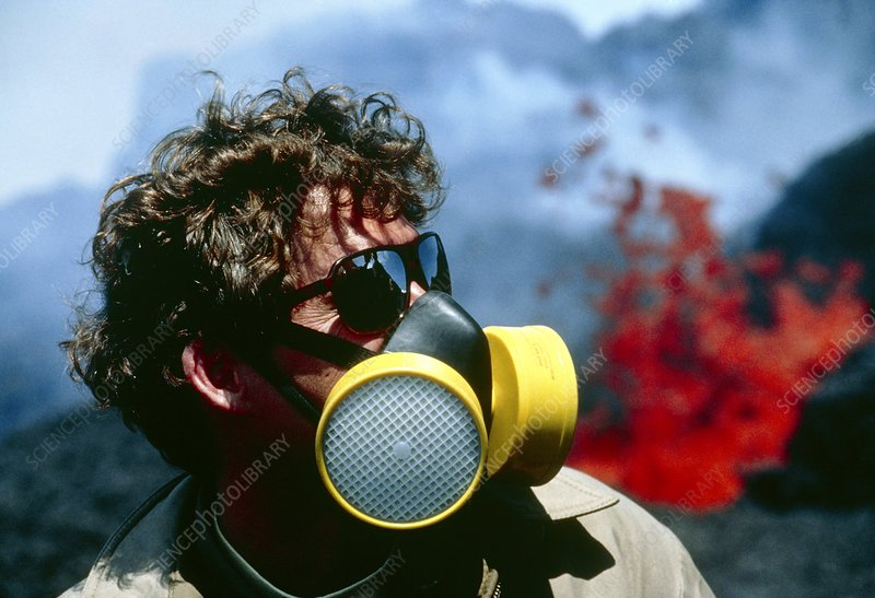 Geologist in breathing mask studying lava flows