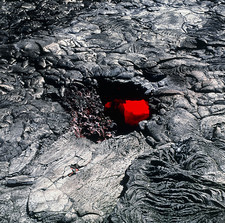 Red molten lava seen through a hole in lava tube