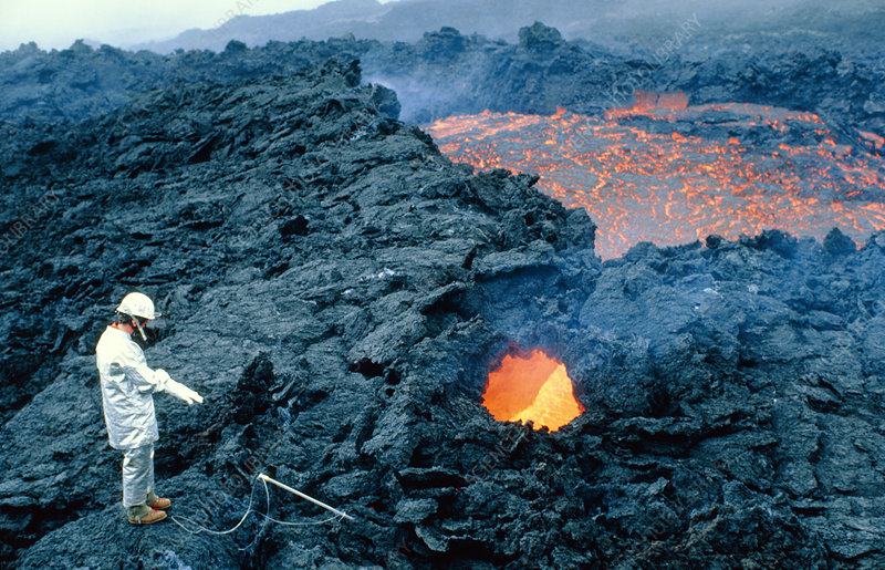 Scientist taking a measurement near a lava flow