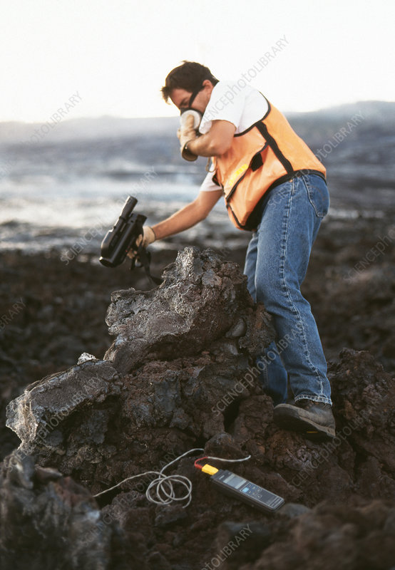 Volcanologist measuring speed of lava flow