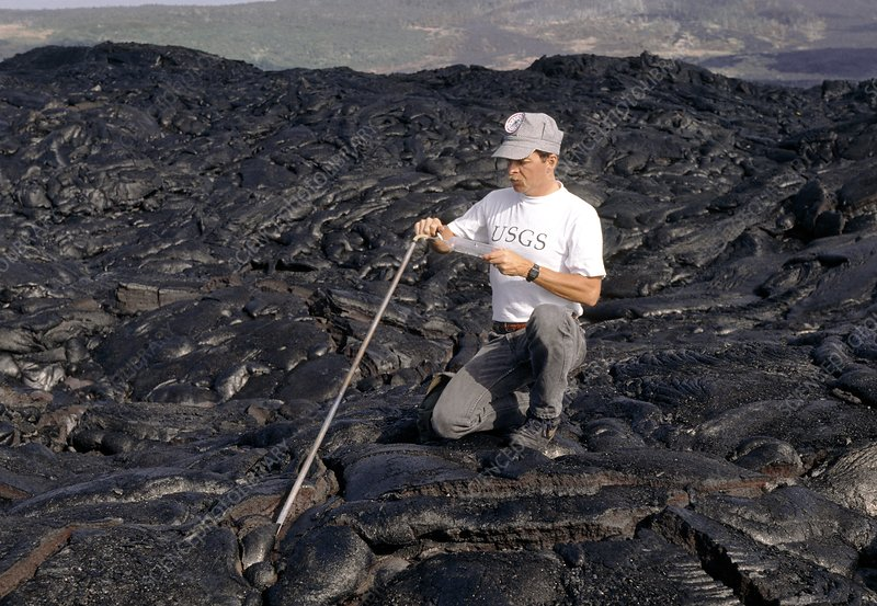 Geologist studying gas sample from lava on volcano