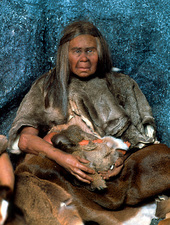 Model of a neanderthal woman holding a baby