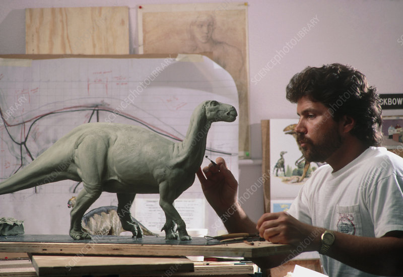 Technician building a clay model of an Iguanodon