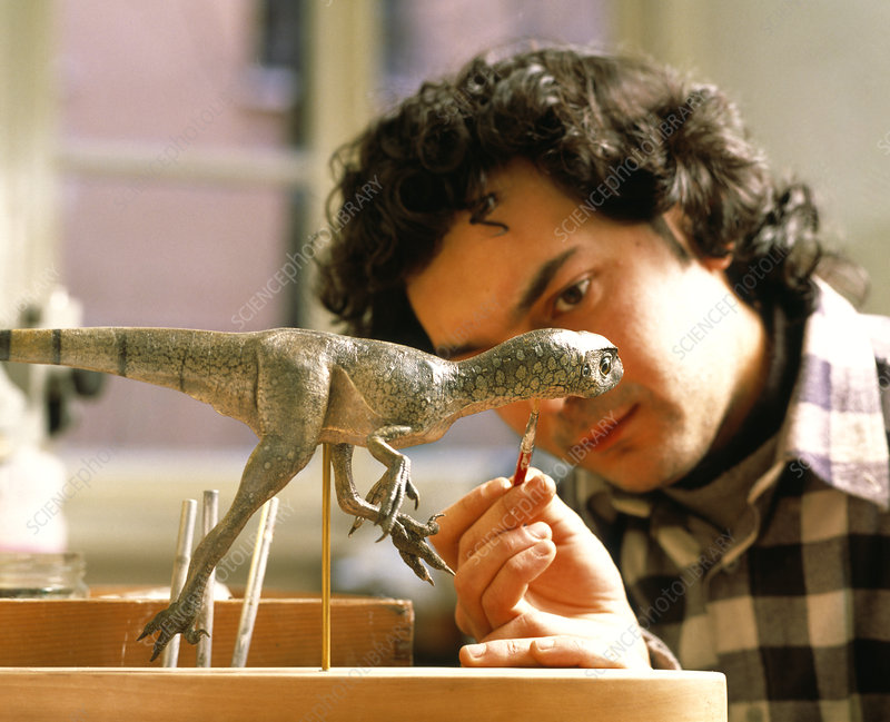Technician painting model of a Scipionyx dinosaur