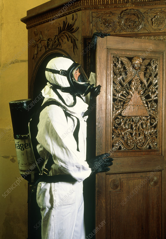 Technician about to fumigate a wooden church door