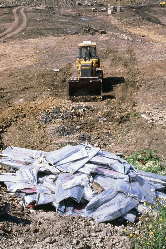 Sacks of asbestos being buried at landfill site