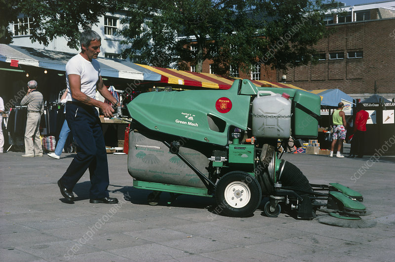 Operator cleaning a square with a large hoover