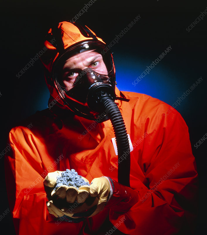 Protected masked worker holds asbestos