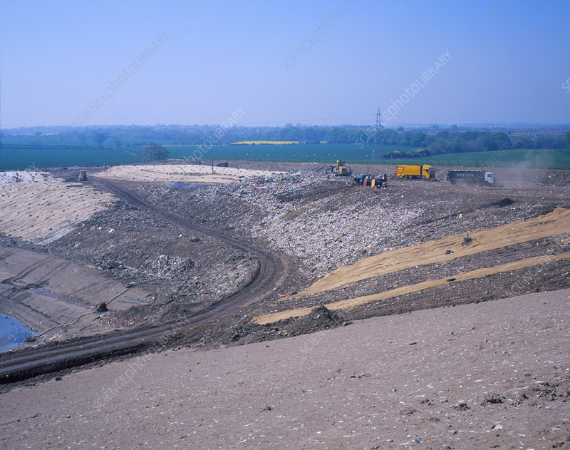 Landfill site with waste trucks and bulldozers