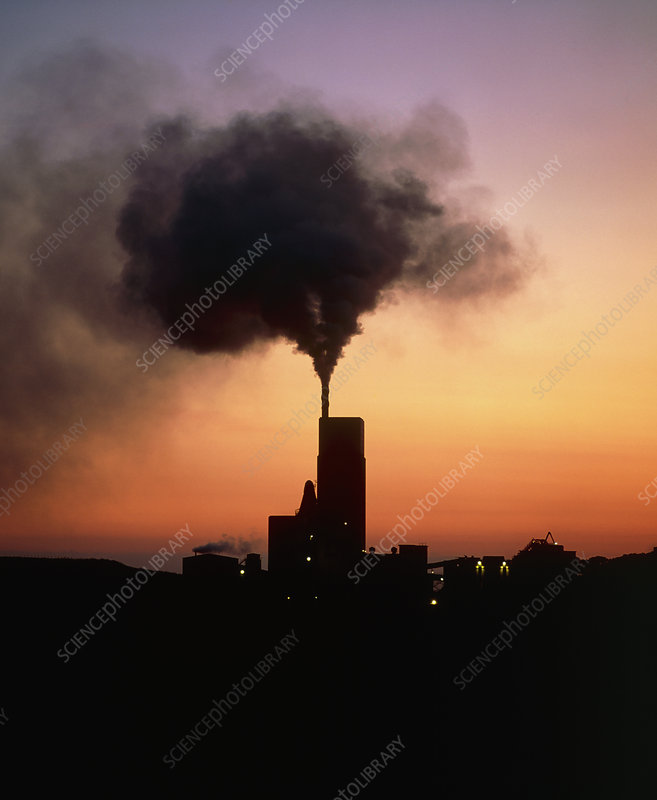 Polluting smoke from cement works chimney at dusk
