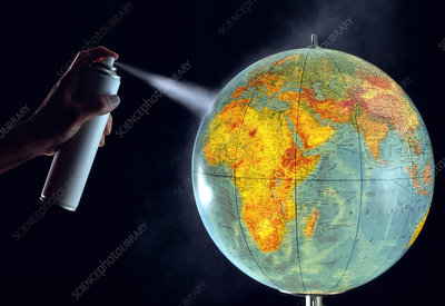 Aerosol spraying onto a globe of Earth.