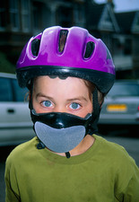 Child cyclist with helmet and anti-pollution mask