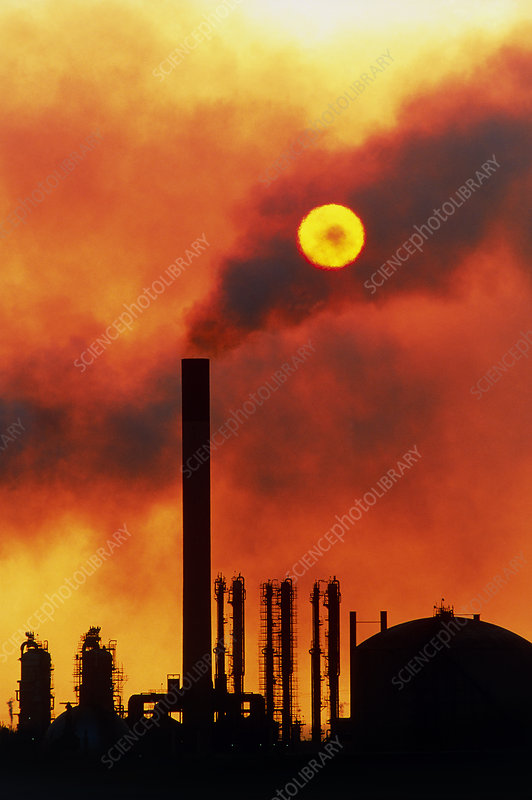 Smoking chimneys of an oil refinery at sunset