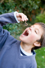 Boy pretending to eat an earthworm
