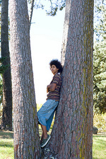 Teenager leaning against a tree