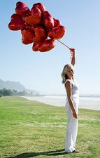 Woman holding heart-shaped balloons
