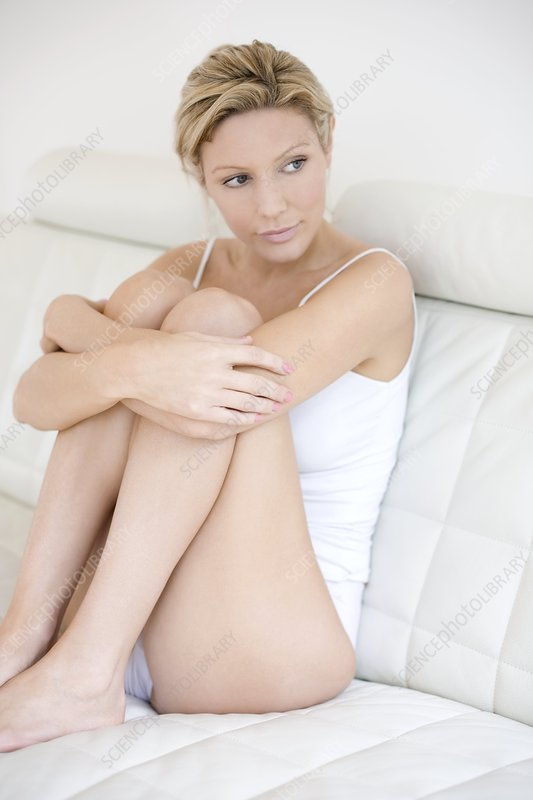 Depressed young woman holding her knees