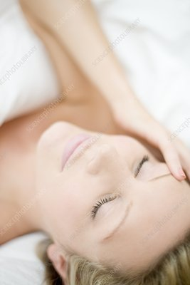 Young woman with a headache lying down
