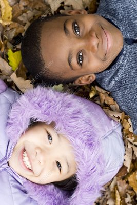 Smiling children lying on autumn leaves