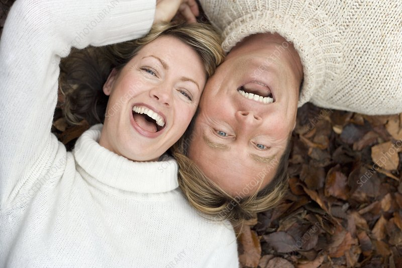 Laughing couple lying on autumn leaves