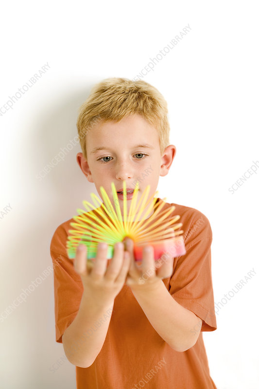 Boy playing with slinky toy