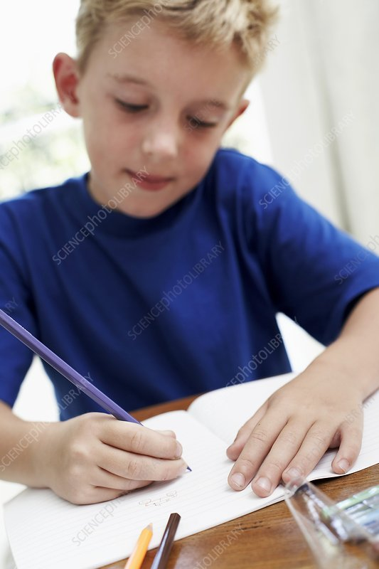 Boy drawing in an exercise book