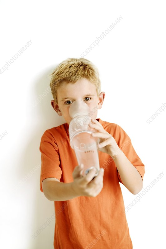 Boy using an asthma spacer