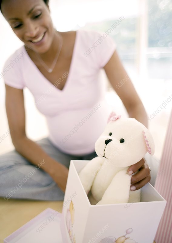 Expectant mother opening baby presents