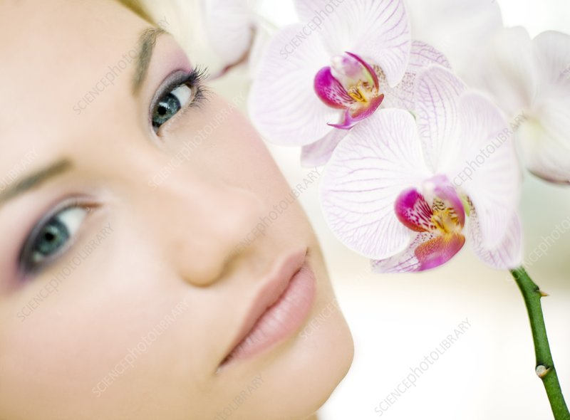 Woman smelling orchid flowers