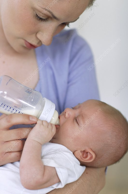 Mother bottle-feeding baby boy