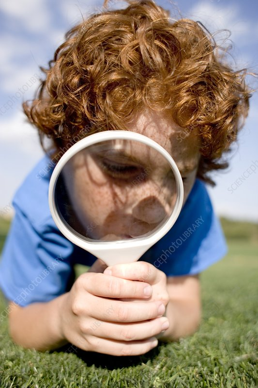 Boy using a magnifying glass