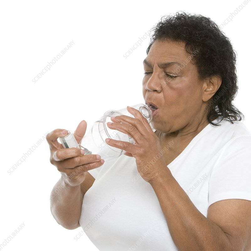 Woman using an asthma spacer