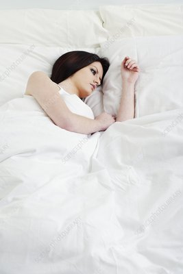 Young woman awake in bed