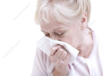 Senior woman blowing her nose