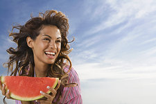 Woman laughing and eating watermelon out