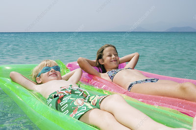 Young boy and young girl floating on inf