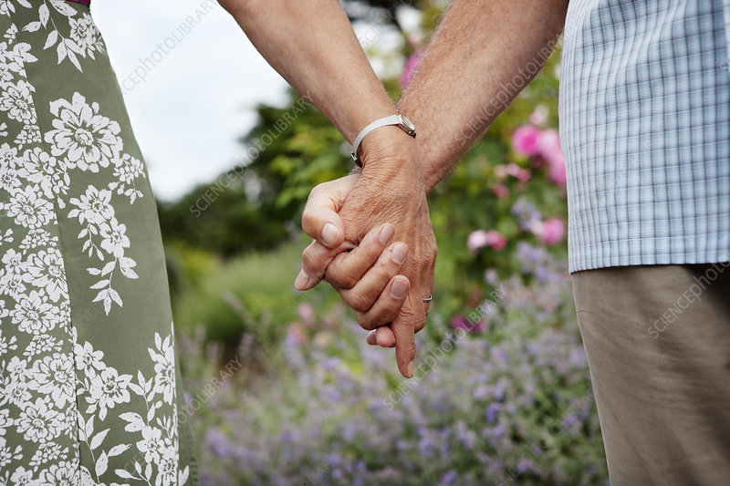 Close-up of mature couple holding hands