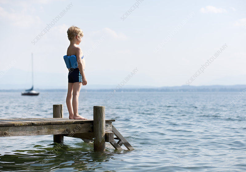 Boy standing on pier with swimming belt