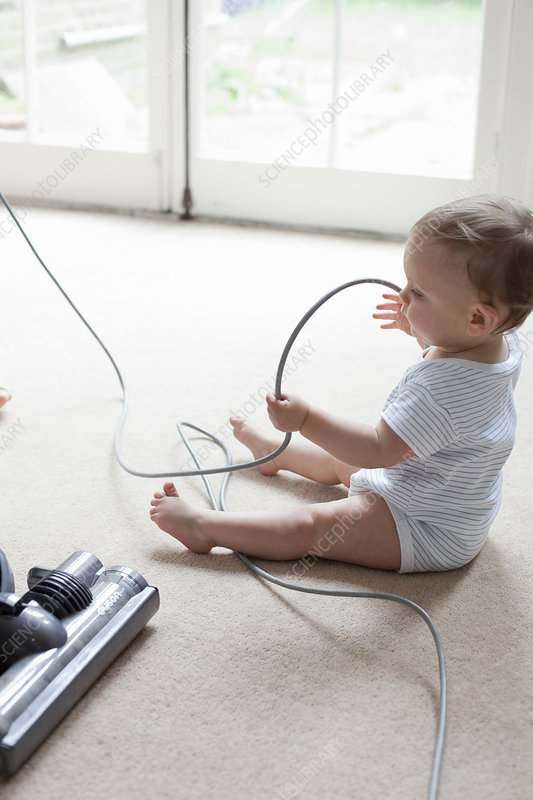 Baby on floor playing with hoover cable