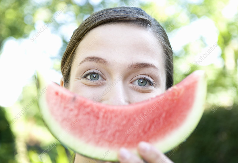 Woman holds up smiley water melon