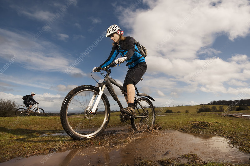 Woman mountain biking in countryside