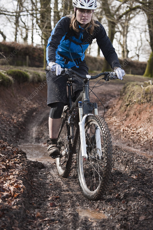 Woman riding mountain bike muddy track