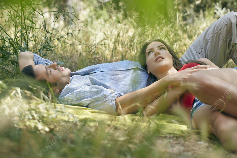 Couple lying on blanket in long grass