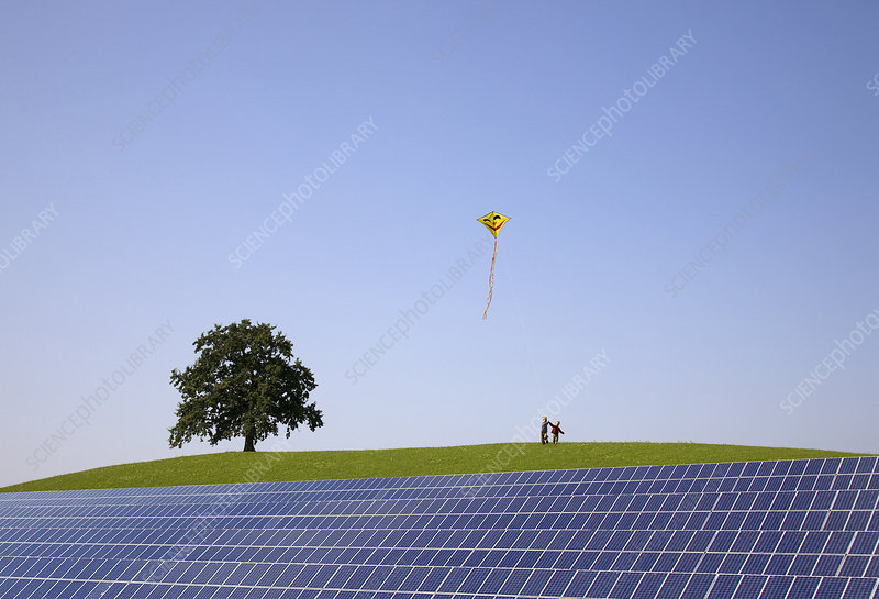 Boys flying kite at solar power station