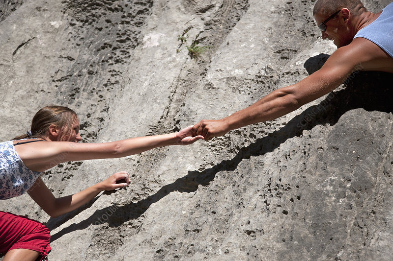 Rock climber helping partner