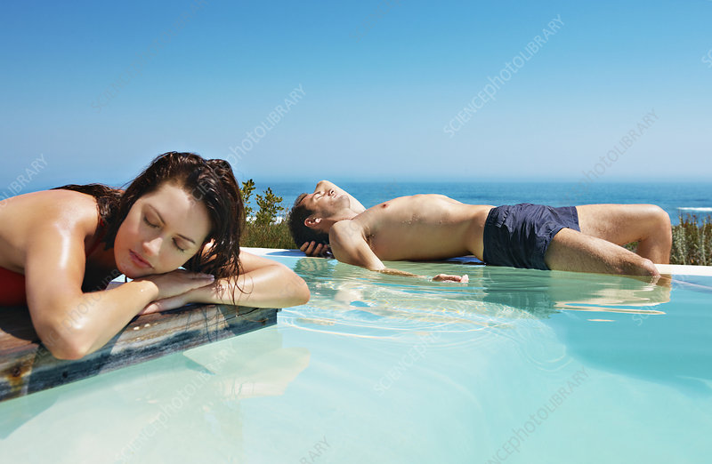 Couple relaxing by infinity pool